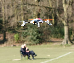 SQ1 mini quadcoper flying against spring treetops with an elderly couple on a park bench watching from below