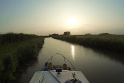 Photo of the front of a canal boat in the Ashby Canal near sunset with fields on either side
