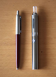 Kanger Evod e-cigarette in silver next to a Parker pen on a wooden surface
