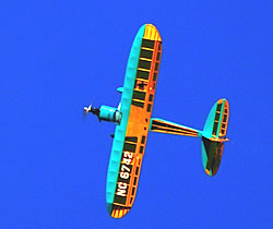 The Phoenix Rainbow trainer plane in orange and turquoise banking towards the camera against a deep blue sky