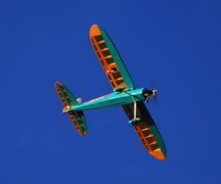 The Phoenix Rainbow trainer plane in orange and turquoise banking away from the camera against a deep blue sky