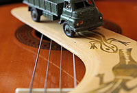Image of a green toy army truck on a boomerange resting on the strings of a guitar