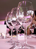 Image of three empty wine glasses on a white table cloth with place fanme with purpe bow, all in pinkish light