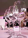 Image of Image of three empty wine glasses on a white table cloth with place fanme with purpe bow, all in pinkish light.
